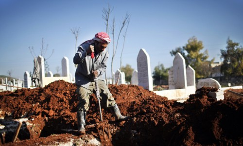 Man digs a grave for a future casualty of Syria's civil war, at Sheikh Saeed cemetery in Azaz city