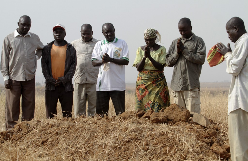 A family gathers around the grave where three murdered family members were buried together in Jos in Nigeria's Plateau state