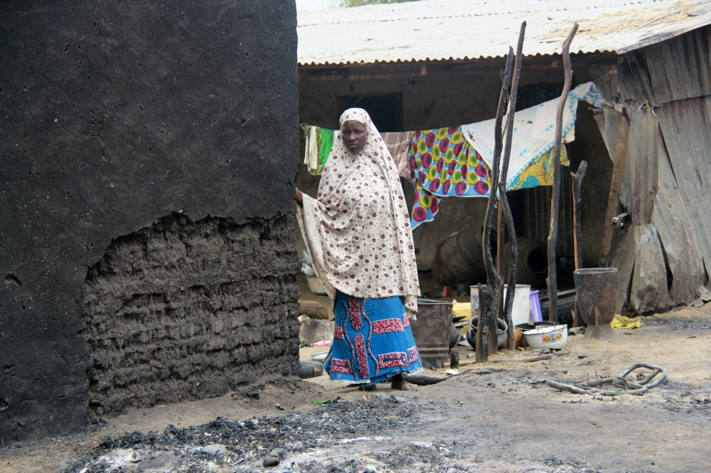 A woman stands next to a burnt house in the aftermath of what Nigerian authorities said was heavy fighting between security forces and Islamist militants in Baga