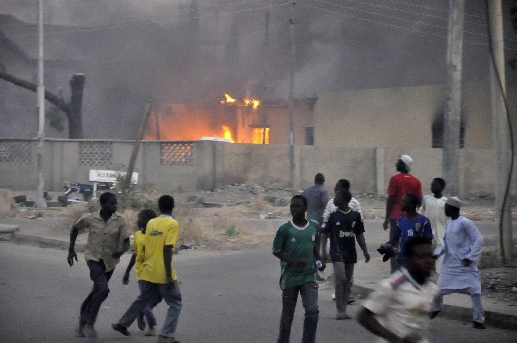 Smoke rises from the police headquarters as people run for safety in Nigeria's northern city of Kano