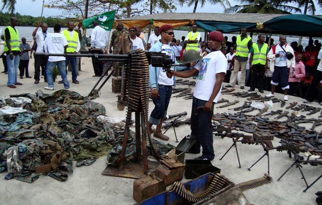 Nigerian militant youths display weapons surrendered by former militants at an arms collection centre at Tourist beach in the oil hub Port Harcourt