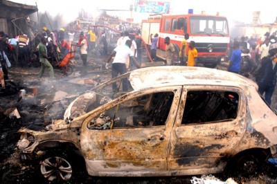 Firefighters and rescuers extinguish a fire at the scene of a bomb blast at Terminus market in the central city of Jos on May 20, 2014. Twin car bombings on Tuesday killed at least 46 in central Nigeria in the latest in a series of deadly blasts that will stoke fears about security despite international help in the fight against Boko Haram Islamists. AFP PHOTO / STR